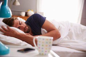 41147087 - sleeping man being woken by mobile phone in bedroom