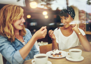 46626158 - two charismatic multi ethnic young girl friends sit at a counter in a cafe enjoying a cup of coffee while laughing and chatting