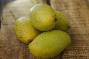 55242674 - closeup picture of four green ripe mangos on ripped brown wooden table background